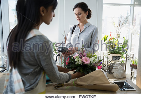 Woman paying with credit card machine flower shop - Stock Photo