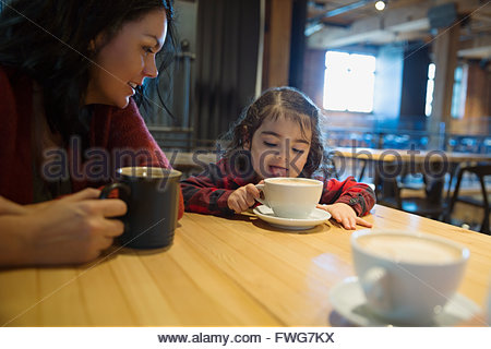 Mother watching daughter lick hot cocoa in a cafe - Stock Photo
