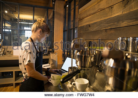 Barista using laptop in coffee shop - Stock Photo