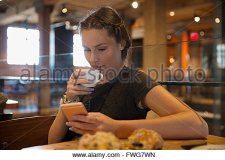 Young woman drinking coffee and texting in cafe - Stock Photo