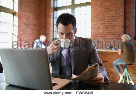 Businessman drinking coffee reading newspaper coffee shop - Stock Photo