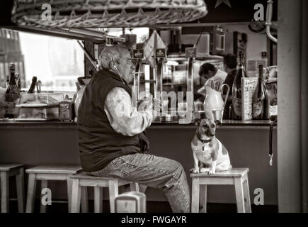 Man and his dog at the bar on a beach. Color version FT7YDY - Stock Photo