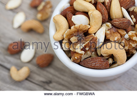 Bowl of mixed nuts on rustic wooden table in natural light. - Stock Photo
