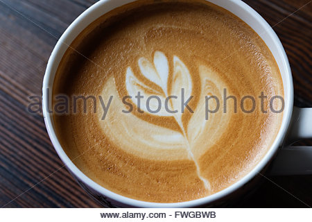 Cup of latte art coffee on wooden table - Stock Photo