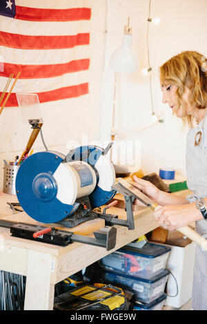 A woman holding a knife shaped steel with a long handle on a rotary grinder. - Stock Photo