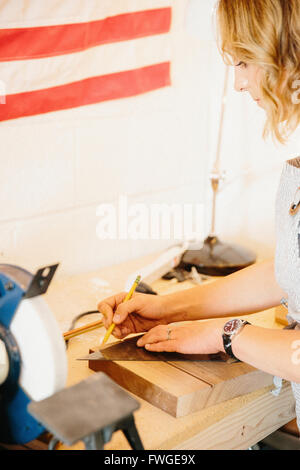 A woman in her workshop using a template to mark wooden blocks. - Stock Photo