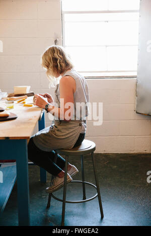 A woman sitting on a stool in a workshop. - Stock Photo