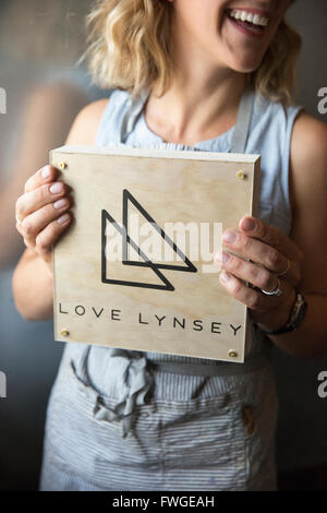 A woman in a blue apron holding her business sign, a square piece of wood with a triangle logo. - Stock Photo