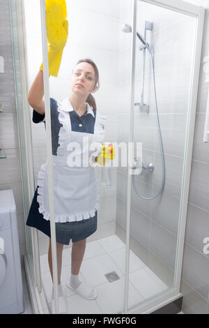 Maid or housekeeper in a neat white apron cleaning a glass shower cubicle with detergent spray - Stock Photo