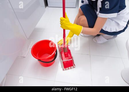 Housekeeper fitting a clean cloth to a mop as she cleans the floor in a white tiled bathroom in a home or hotel - Stock Photo