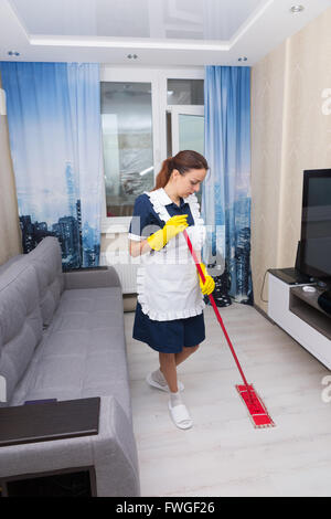 Housekeeper cleaning a hotel suite mopping the floor between a comfortable sofa and wall mounted television - Stock Photo