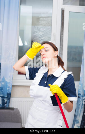 Tired hot housekeeper or maid standing holding a mop or broom wiping her forehead with a gloved hand, close up view - Stock Photo