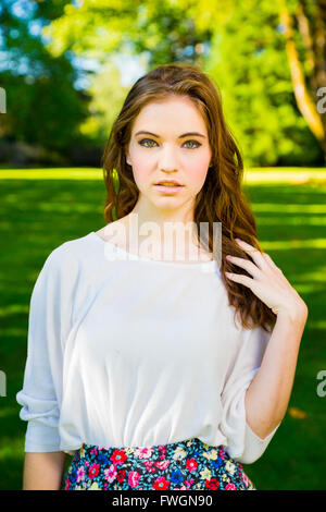A beautiful young girl poses for a fashion style portrait outdoors at a park with natural lighting. - Stock Photo