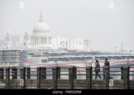 Couple on a pier overlooking St. Paul's Cathedral on the banks of the River Thames, South Bank, London, England, - Stock Photo