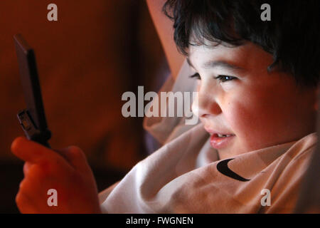 Young boy playing computer console - Stock Photo