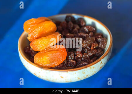 Dried apricots and raisins in little plate on blue background - Stock Photo