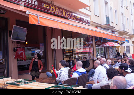 People watching a football match in a terrace in the street. UEFA 2016.  Berlin, Euro Champions League. - Stock Photo