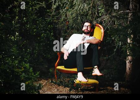 Portrait Of Young Man Sitting On Chair By Trees - Stock Photo