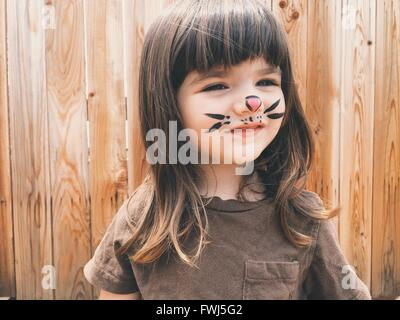 Close-Up Of Smiling Cute Girl With Painting On Face Standing Outdoors - Stock Photo
