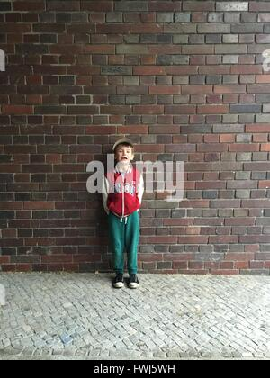 Portrait Of Boy Crying While Standing Against Brick Wall - Stock Photo