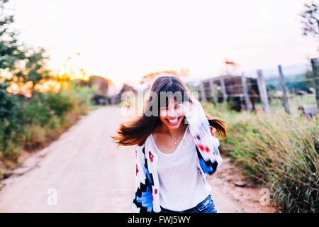 Portrait Of Happy Young Woman Running On Road Amidst Plants Against Clear Sky - Stock Photo