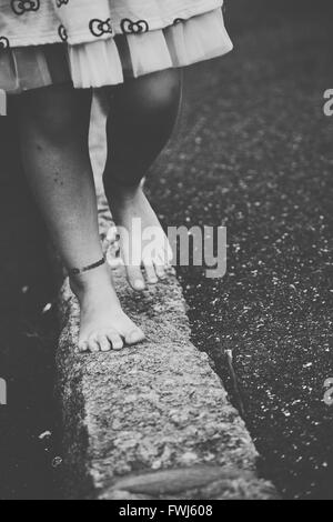 Low Section Of Girl Walking On Retaining Wall - Stock Photo