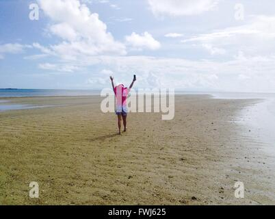 Rear View Of Happy Woman With Hands Raised Walking On Beach Against Sky - Stock Photo