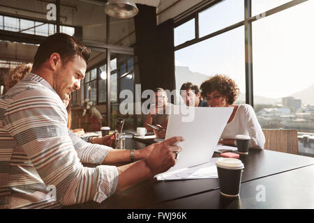 Portrait of young businessman explaining business plan to his colleagues while sitting in office. - Stock Photo