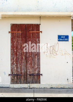 A wooden old door and plate with name of the street, rue du General de Gaulle, in Saint Paul on the island of La - Stock Photo