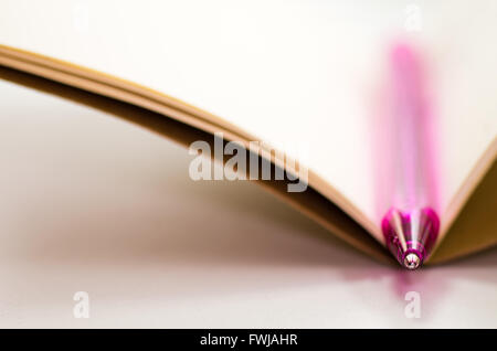 Pink Pen On Open Notebook At Table - Stock Photo