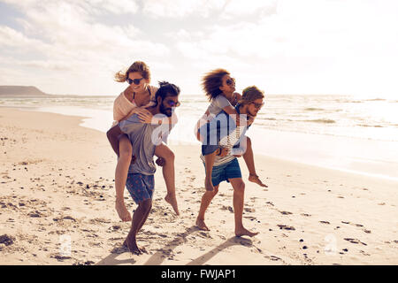 Two beautiful young couples walking along the beach, with men giving piggyback ride to women. Piggyback games on - Stock Photo