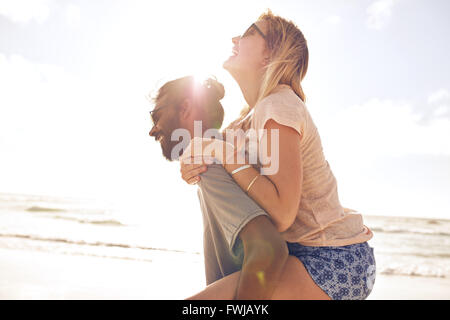 Side view portrait of young man carrying his girlfriend on his back at the beach. Man piggybacking girlfriend at - Stock Photo