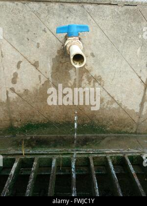 Close-Up Of Water Running From Faucet In Sewage - Stock Photo