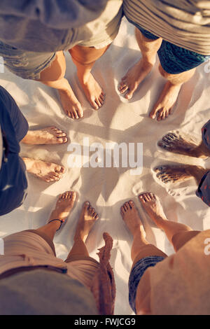 Top view image of diverse group of friends standing barefoot in circle on sandy beach. Feet of young people standing - Stock Photo