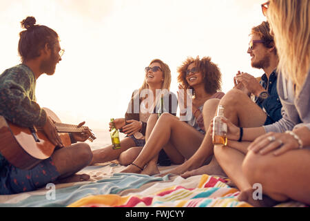 Happy hipsters relaxing and playing guitar at the beach. Friends drinking beers and listening to music. Having fun - Stock Photo