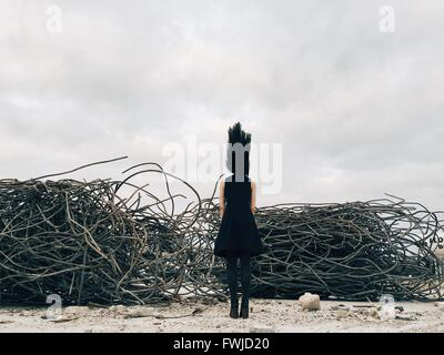Full Length Rear View Of Woman With Tousled Hair Standing By Abandoned Metal Against Sky - Stock Photo
