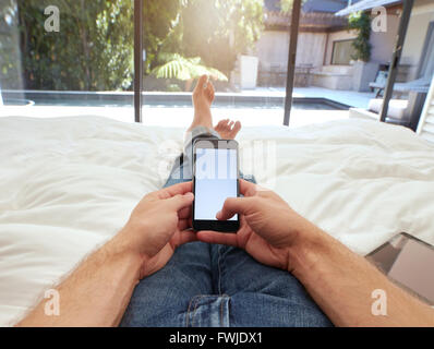 Closeup image of man lying on a bed holding a mobile phone with blank screen. POV shot of man relaxing in bedroom - Stock Photo