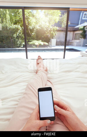 POV shot of a woman using mobile phone while lying on bed. Human hand holding smart phone with blank screen in bedroom. - Stock Photo