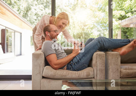 Indoor shot of mature couple at home using digital tablet and smiling. Man is sitting on sofa with woman standing - Stock Photo