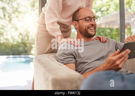 Indoor shot of a smiling man sitting on sofa using digital tablet with woman standing behind him. - Stock Photo