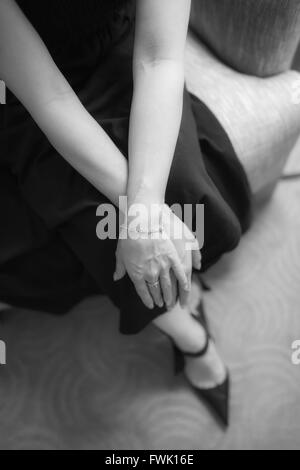 Midsection Of Woman Sitting On Armchair At Home - Stock Photo