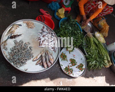 Low Section Of Vendor Selling Vegetables And Fish In Market - Stock Photo