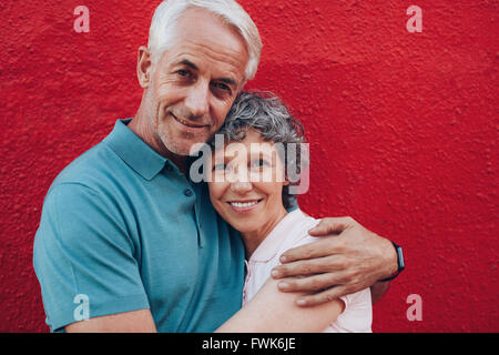 Portrait of loving middle aged couple embracing against red background. Mature man and woman together against red - Stock Photo