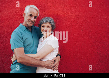 Portrait of loving middle aged man and woman standing together against red background. Senior couple embracing against red wall Stock Photo