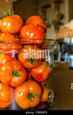 Close-Up Of Tomatoes In Jar On Table - Stock Photo