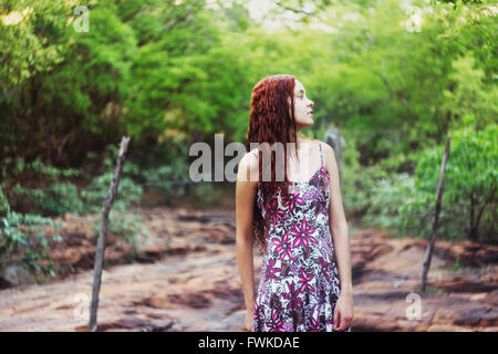 Young Woman Standing Against Trees On Field