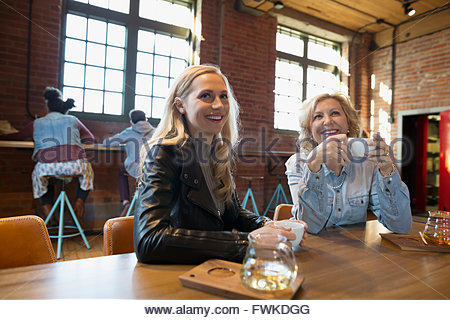 Smiling mother and daughter drinking tea in coffee shop - Stock Photo