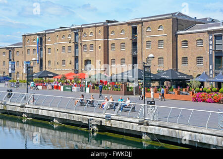 Outdoor restaurant & converted warehouses beside North Dock of old West India Docks at Canary Wharf London Docklands, - Stock Photo