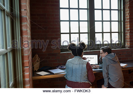Boy and girl using laptop in coffee shop - Stock Photo