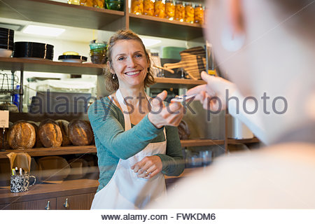Customer paying bakery owner with credit card - Stock Photo